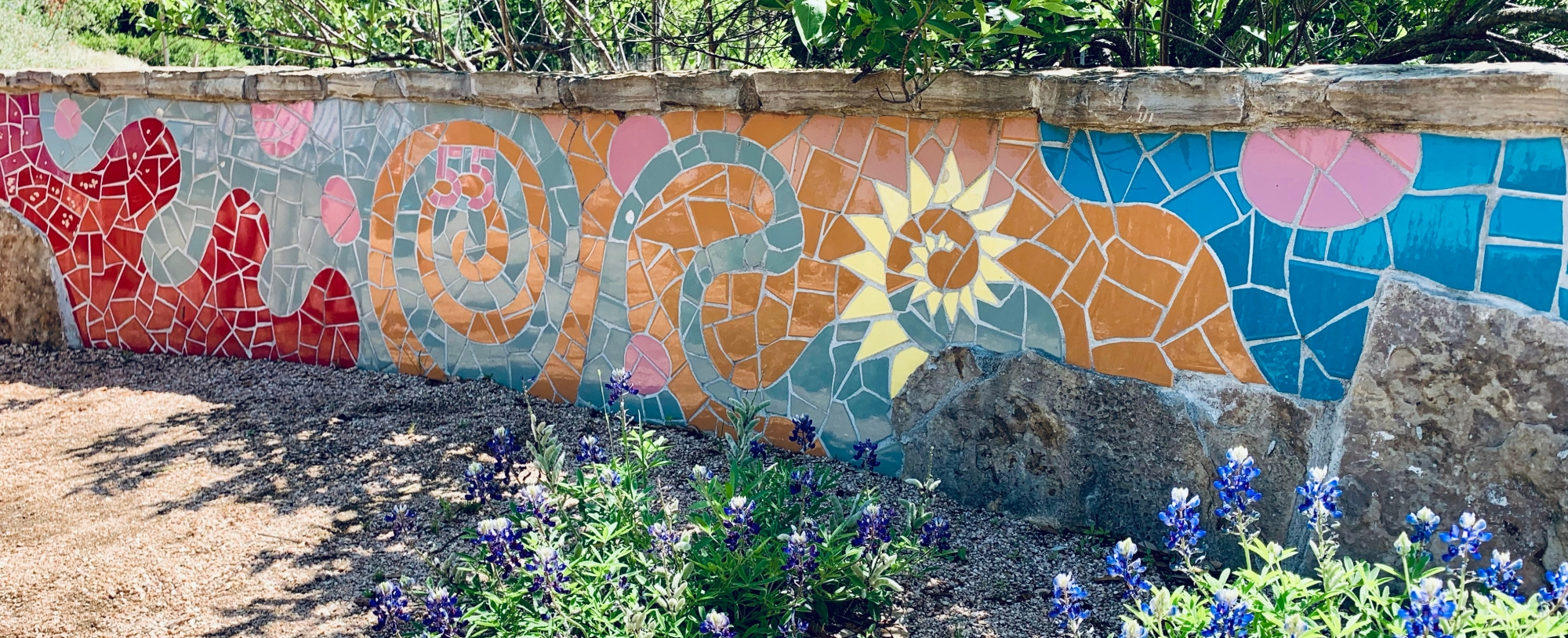 mosaic mural on low stone wall, with bluebonnet flowers